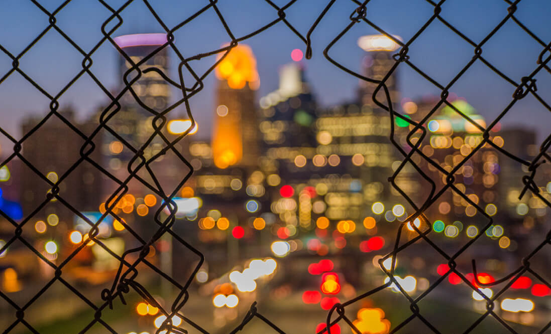 Holes in a wire fence framing a view of downtown Minneapolis.